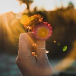 woman holding flower with sunrise in background